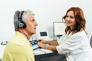 a doctor using audiology equipment to test for hearing loss
